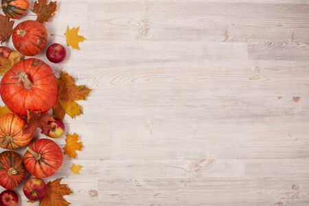 Photo pour Festive autumn still life  with pumpkins, red apples and leaves on light  wooden background. Top view with copy space. Concept of autumn harvest, happy Thanksgiving  day or Halloween. - image libre de droit