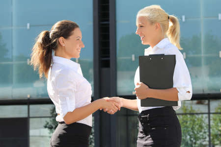Photo for two young beautiful business women shaking hands in street - Royalty Free Image