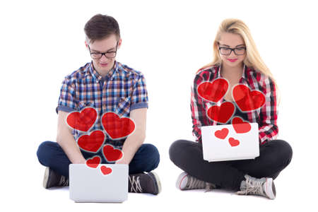 Photo for online dating concept - young man and woman sitting with laptops and sending love messages isolated on white background - Royalty Free Image