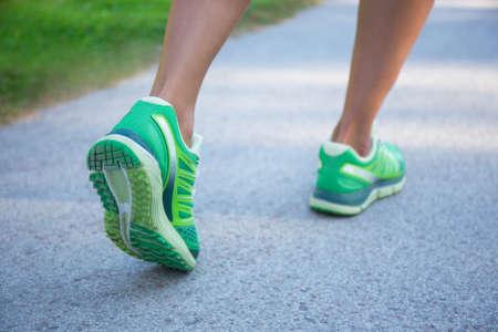 Photo pour close up of jogging woman in green running shoes - image libre de droit