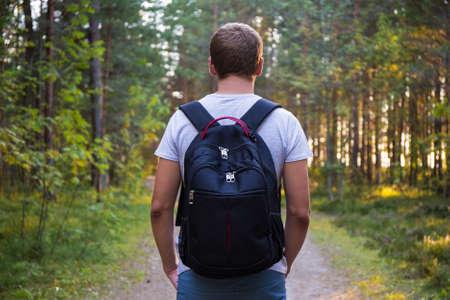 Foto de rear view of man with backpack hiking in forest - Imagen libre de derechos