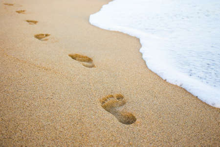 Foto de close up of footprints in the sand and sea wave - Imagen libre de derechos