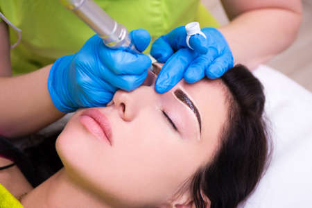 Foto de close up of cosmetologist applying permanent make up on female eyebrows - Imagen libre de derechos