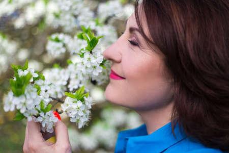 Foto de close up portrait of happy middle aged woman smelling cherry tree branch in spring garden - Imagen libre de derechos