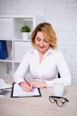 Foto de business plan concept - cheerful mature business woman working in office, writing something on clipboard - Imagen libre de derechos