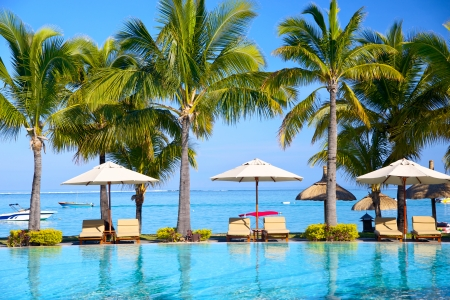 Photo for Swimming pool with  lounge chairs and umbrellas on beach in Mauritius - Royalty Free Image