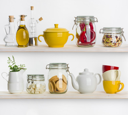 Kitchen shelves with various food ingredients and utensils on white