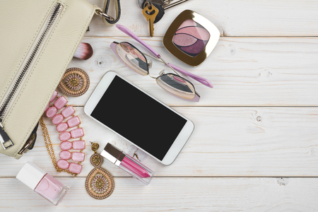 Photo pour Female things falling from handbag on wooden background with copyspace - image libre de droit