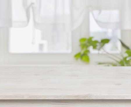 Foto de Wooden table over defocused green leaves and curtained window background - Imagen libre de derechos