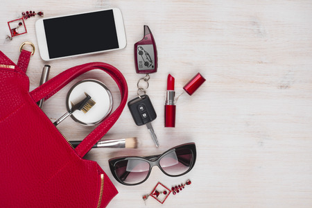 Photo pour Female things and red handbag on wooden background with copyspace - image libre de droit