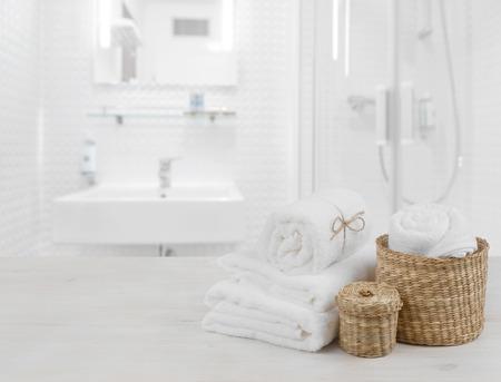 Foto de White spa towels and wicker baskets on defocused bathroom interior - Imagen libre de derechos