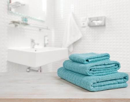 Foto de Turquoise spa towels pile on wood over blurred bathroom background - Imagen libre de derechos