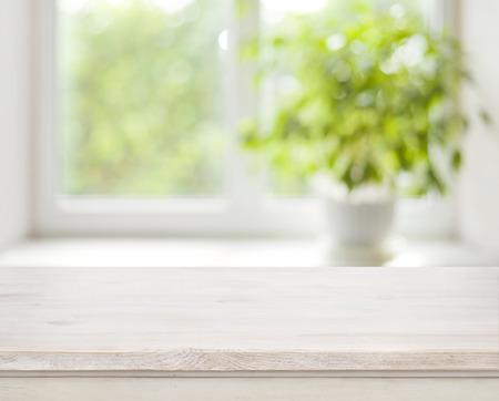 Foto de Light wooden table on defocuced spring window background - Imagen libre de derechos