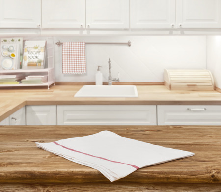 Photo for Wooden dinning table with napkin in front of blurred kitchen - Royalty Free Image