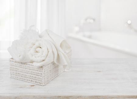 Foto de Towels and bath sponge in box over blurred bathroom background - Imagen libre de derechos