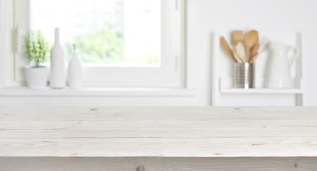 Foto de Wooden table on blurred background of kitchen window and shelves - Imagen libre de derechos