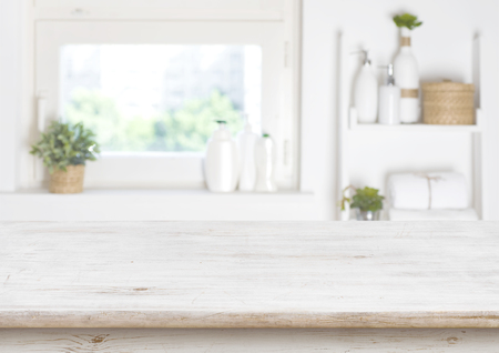 Foto per Wooden table on blurred background of bathroom window and shelves - Immagine Royalty Free