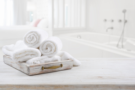Photo for Vintage drawer with white towels over blurred bathroom and bedroom - Royalty Free Image