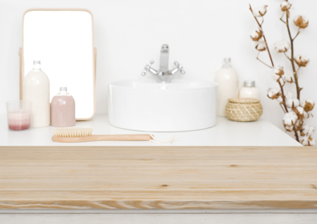 Foto de Wooden table top for product display and blurred bathroom - Imagen libre de derechos