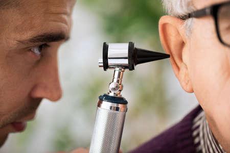 Foto de Doctor specialist Performs an Ear Examination close up - Imagen libre de derechos