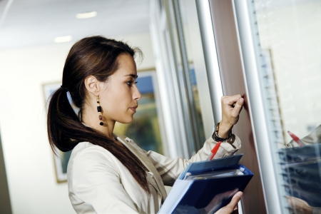 Office life: young secretary knocking on her bossÕ door