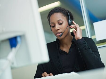 female african american customer service representative with headset typing on computer. Horizontal shape, front view, waist up