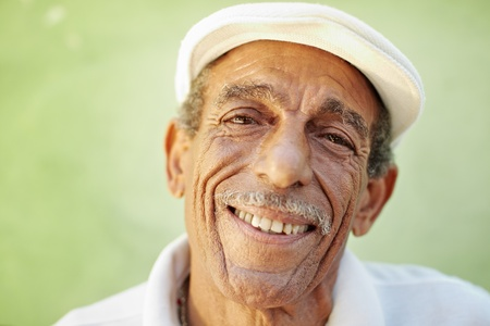 portrait of senior hispanic man with white hat looking at camera against green wall and smiling. Horizontal shape, copy space