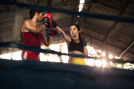 Young woman exercising with trainer at boxe and self defense lesson. Copy space