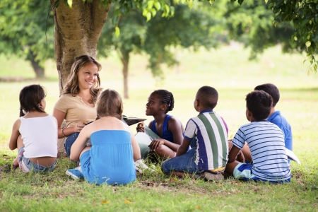 Children and education, young woman at work as educator reading book to boys and girls in park
