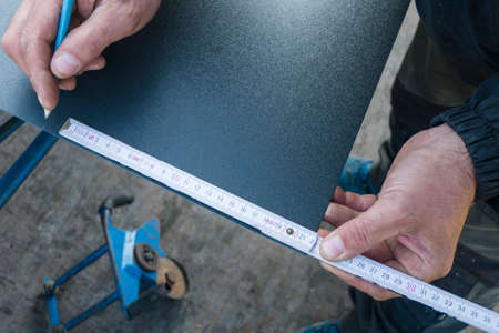 Photo pour Roofer working with a meter to make markings on a metal sheet - image libre de droit