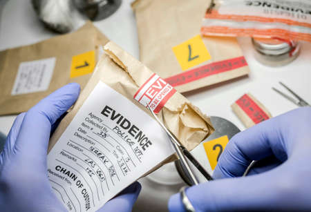 Foto de Scientific police opens with scissors a bag of evidence of a crime in scientific laboratory - Imagen libre de derechos
