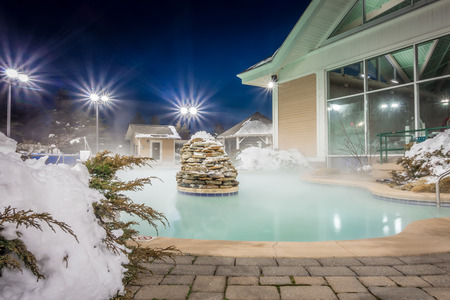 Photo for hot tubs and ingound heated pool at a mountain village in winter at night - Royalty Free Image