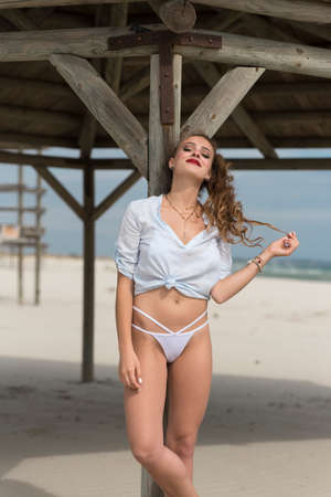 Photo for Young cute woman pose against big wooden shelter on the beach wear bottom white bikini and tied shirt - Royalty Free Image