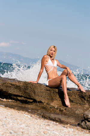 Photo for Tall slim blonde woman wear white sexy bikini sitting on rocks, waves crashing on rocks, sea sky and clouds as background - Royalty Free Image