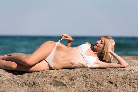 Photo for Tall slim blonde woman wear white sexy bikini lying on rocks, sea sky and clouds as background - Royalty Free Image