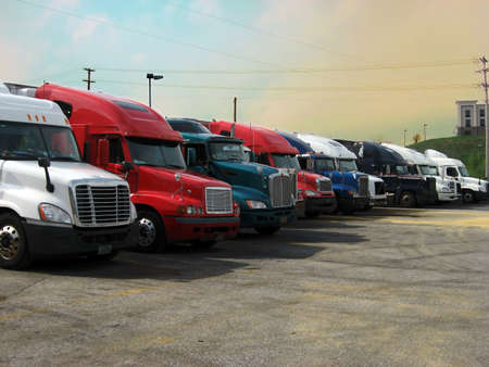 A row of big semi trucks in various colors parked at a truck stop at sunset.