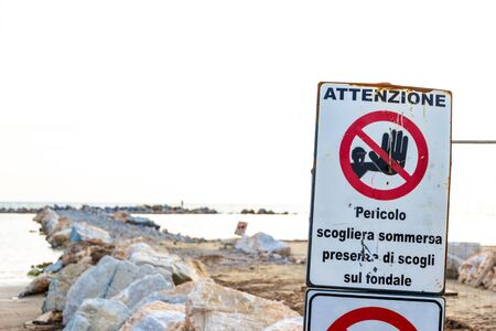 Photo for Warning signs reading: 'Warning. Danger submerged reef, rocks on the shoal are present' near a construction site on the shoreline in Follonica, Italy - Royalty Free Image