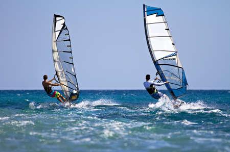 Foto de Back view of two windsurfers in action mooving parallel to eath other - Imagen libre de derechos