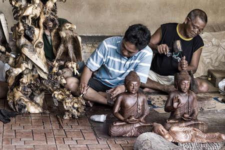 Photo pour Men are making wooden crafts. Bali. Ububd. Indonesia - image libre de droit