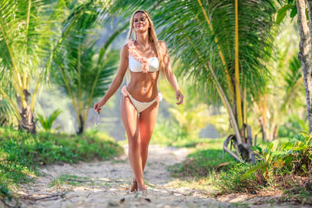 Photo pour Beautiful woman in white bikini walking between palm trees at the tropical beach. Karon, Phuket, Thailand - image libre de droit