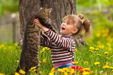 Funny lovely little girl playing with a cat
