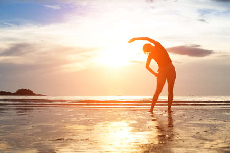 Foto de  Silhouette young woman, exercise on the beach at sunset - Imagen libre de derechos