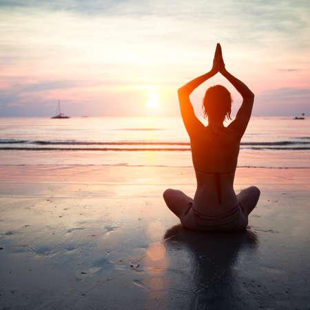 Foto de Silhouette of a woman yoga on sea sunset. - Imagen libre de derechos