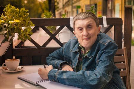 Foto de Disabled man writing in a notebook sitting at an outdoor cafe.  - Imagen libre de derechos