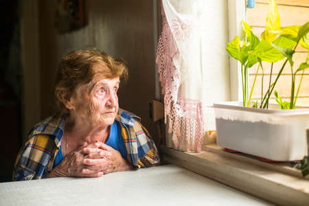 Foto de Lonely old woman sitting by the window in his cottage. - Imagen libre de derechos