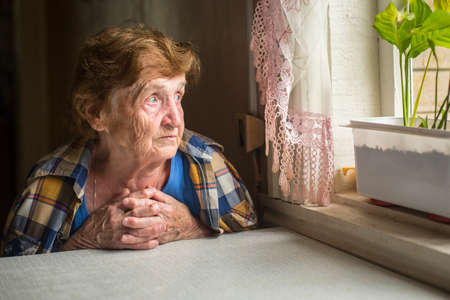 Photo pour Old lonely woman sitting near the window in his house. - image libre de droit