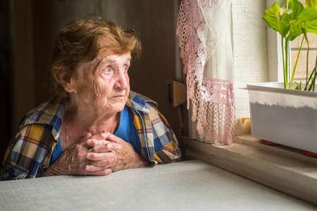 Foto de Old lonely woman sitting near the window in his house. - Imagen libre de derechos