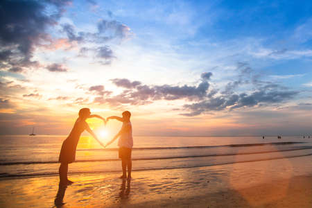 Photo pour Young couple of lovers on a tropical beach holding hands forming a heart. - image libre de droit