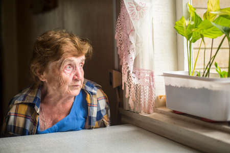 Photo pour Old woman sitting alone near the window in his house. Loneliness in old age. - image libre de droit