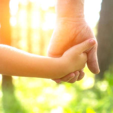 Foto de Adult holding a child's hand, close-up hands, nature in background. - Imagen libre de derechos
